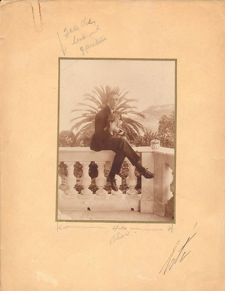 """A rare signed image of a young Erte. Original Photograph Signed, 8vo, attached to a folio board, stamped on verso, """"Harper's Bazar, 1/15/19"""". With Autograph Note unsigned, in French, on his business card, 1962. ERTÉ, Romain de Tirtoff."""