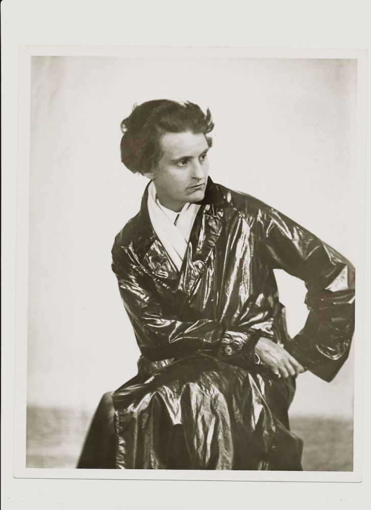 Modern Print Signed by Abbott on verso, 10 x 8, of Sylvia Beach in her long dark trench coat seated, three-quarter length, originally photographed in 1927, printed later (ca 1960s-70s.). BERENICE ABBOTT, SYLVIA BEACH.