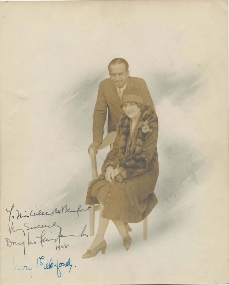 Photograph Signed by both Fairbanks and Pickford, 8 x 10 inches, silver gelatin print in soft brown and gray tones, 1928. Sjhe sits in a chair wearing fur trimmed coat and hat and he leans on the back of the chair dressed n suit and tie. DOUGLAS FAIRBANKS, MARY, AND PICKFORD, SR.