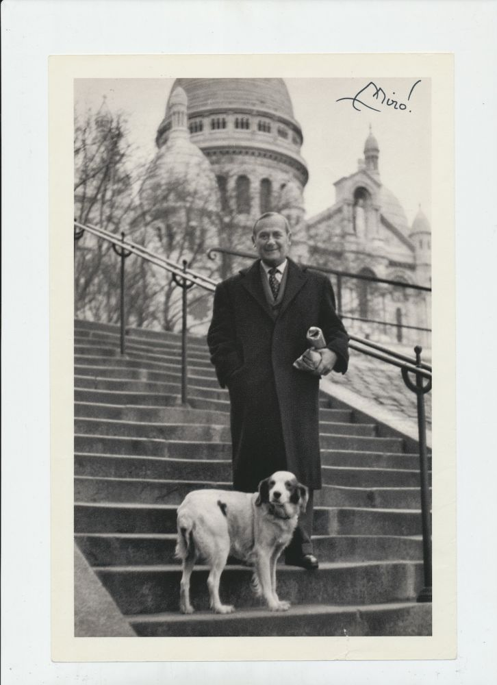 Photograph Signed, black and white page from a book, 4to, showing Miro full length, standing on outdoor steps dressed in suit with top coat, with his dog. JOAN MIRO.
