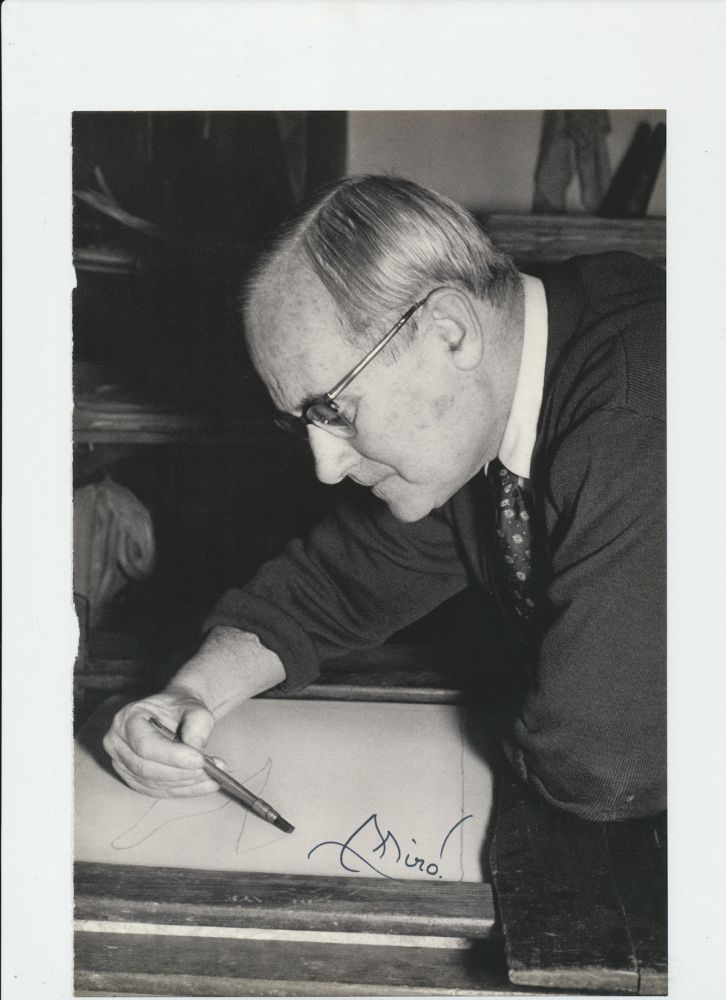 Photograph Signed, black and white page from a book, 4to, showing Miro head and shoulders leaning as he draws a sketch. JOAN MIRO.