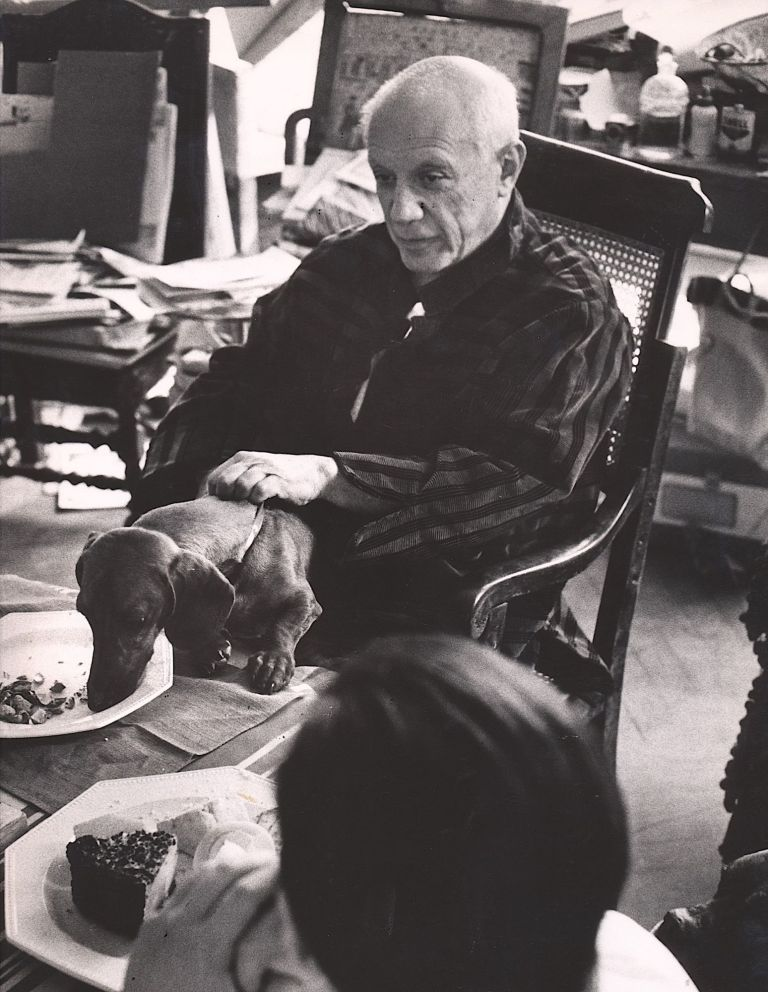 Large photograph of Picasso with Lump, his beloved dachshund; black and white gelatin silver print, photographer's stamp on verso and trim markings also on verso. PICASSO, DAVID DOUGLAS DUNCAN.
