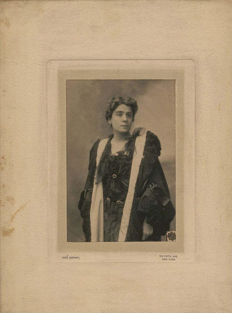 "Large Photograph Signed of the famed actress as Magda in the play ""Heimat"" by dramatist Hermann Sudermann. On verso using her familiar purple ink, she dedicates, signs and dates the photograph ""To Mr. B. Webster E. Duse 1896, New York."" The photograph was taken in New York by photographer Aime Dupont. It measures 5.5 x 7.25 on hard board measuring 10 x 11.75. ELEONORA DUSE."