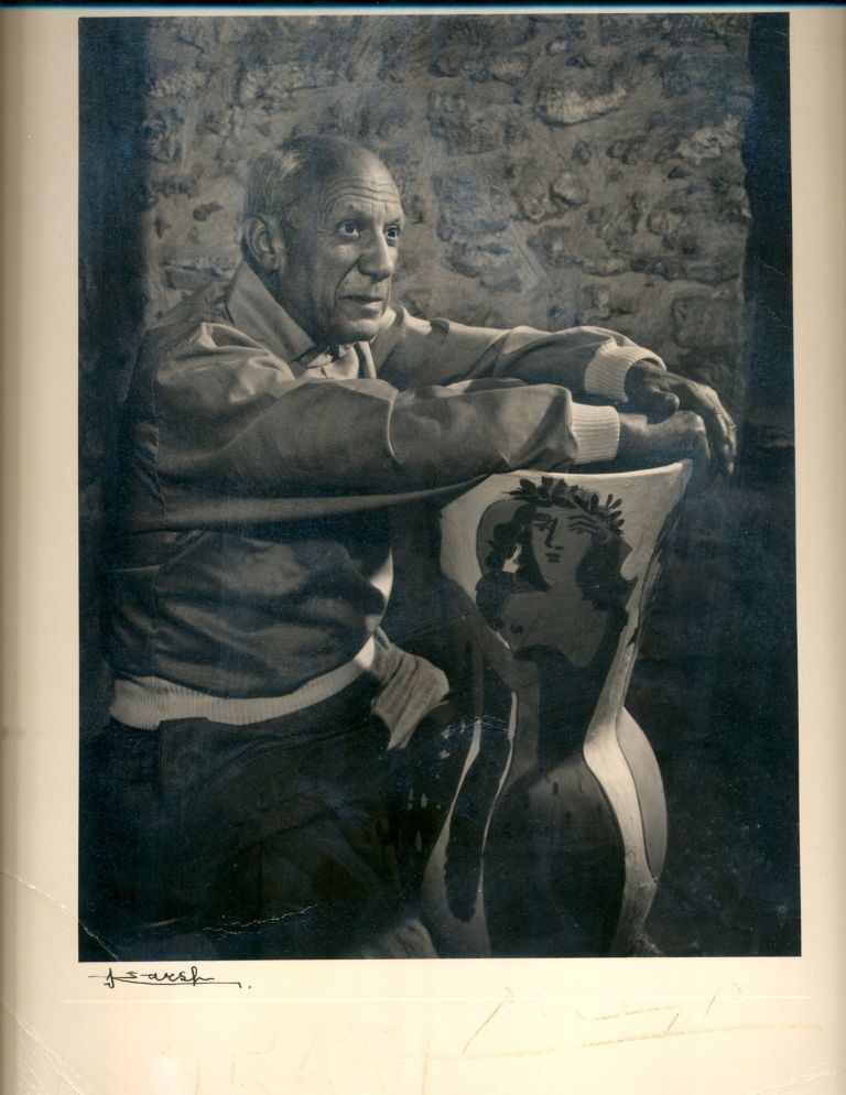 Photograph by Karsh of Picasso with large vase, black and white. Signed by Karsh in dark pen, on photograph mount, and signed by Picasso in light pencil which has faded on the first white mat of the triple matted image. Second mat is brick red surrounded by dominant tan mat board. Framed in white wood frame measuring 13 x 18 inches. YOUSUF KARSH PHOTOGRAPH of PABLO PICASSO, BOTH.