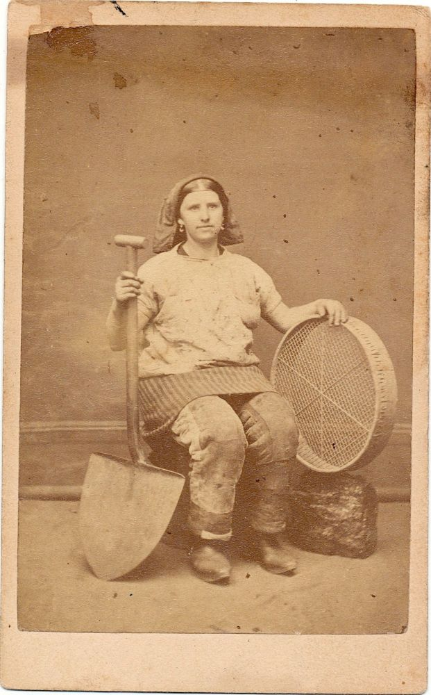 Photograph of Pit Brow Lass (Female Coal Miner) in work clothes with tools. PIT BROW LASS.