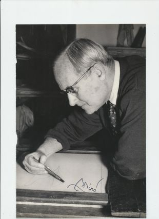 Photograph Signed, black and white page from a book, 4to, showing Miro head and shoulders leaning as he draws a sketch.